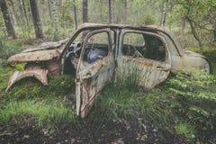 Vieille voiture rouillée de chute dans une forêt photo stock