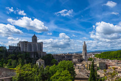 Vieille vue de ville de Gérone avec les montagnes vertes et le ciel bleu avec des nuages Photographie stock libre de droits