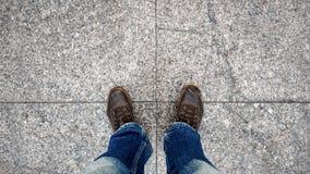 Vieille vue supérieure en cuir d'espadrilles et de blues-jean de jambe sur le pavé Images stock