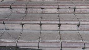 Vieilles étapes en pierre marron couvertes de graphite avec la vue de face d'éraflures et de fissures Photos libres de droits