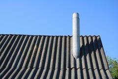 Vieilles ardoises et cheminée de toit d'amiante de toit contre le ciel bleu Images libres de droits