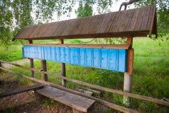 Vieilles boîtes aux lettres bleues rouillées dans une rangée Images stock