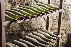 Vieilles bouteilles de vin poussiéreuses dans la cave foncée Photographie stock