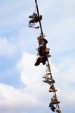 Vieilles chaussures accrochant sur le fil électrique contre un ciel bleu Photo libre de droits