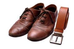 Vieilles chaussures brunes et ceinture brune sur un fond blanc d'isolement Image libre de droits