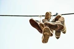 Vieilles chaussures de sport jetées au-dessus du câble noir Images libres de droits