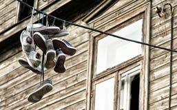 Vieilles chaussures de sport jetées au-dessus du câble noir avec la maison à l'arrière-plan Photographie stock