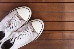 Vieilles chaussures de toile sur un plancher en bois Image stock
