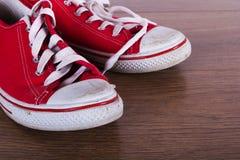 Vieilles chaussures de toile sur un plancher en bois Photo stock