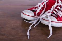 Vieilles chaussures de toile sur un plancher en bois Photographie stock