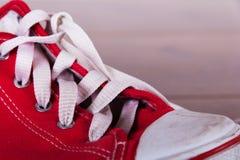 Vieilles chaussures de toile sur un plancher en bois Photographie stock libre de droits