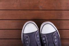 Vieilles chaussures de toile sur un plancher en bois Photo libre de droits