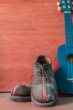 Vieilles chaussures et ukulélé Images stock