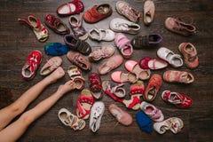 Vieilles chaussures portées de bébé (enfant, enfant) sur le plancher sandales, bottes, s Images stock