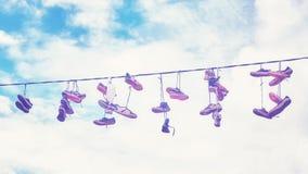 Vieilles chaussures sales accrochant sur le fil Image stock