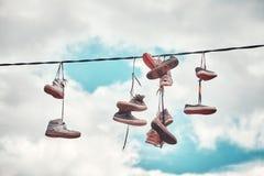 Vieilles chaussures sales accrochant sur le fil Photographie stock