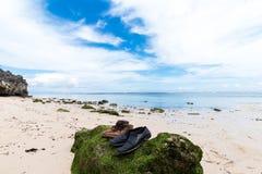 Vieilles chaussures sur la grande pierre avec de la mousse Petites roches dispersées sur la fin de sable de plage  Beau paysage d photo stock
