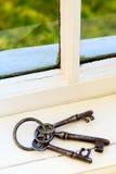 Vieilles clés sur le rebord de fenêtre par la fenêtre Photos libres de droits