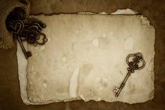 Vieilles clés sur le vieux fond de papier Image stock