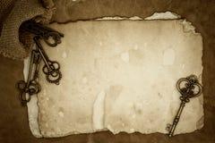 Vieilles clés sur le vieux fond de papier Photos stock
