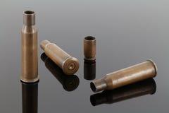 Vieilles douilles de fusil et de pistolet/enveloppes de balle sur un fond foncé de miroir Photos stock