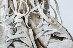 Vieilles espadrilles blanches sur le fond blanc Photo libre de droits