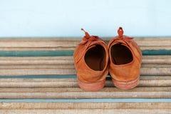 Vieilles espadrilles d'enfants un fond en bois Photos stock