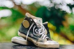 Vieilles espadrilles de noir de chaussures avec le fond de bokeh Photographie stock