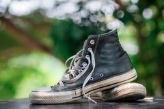 Vieilles espadrilles de noir de chaussures avec le fond de bokeh Photos stock