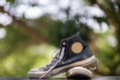 Vieilles espadrilles de noir de chaussures avec le fond de bokeh Images stock