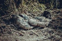 Vieilles espadrilles grises sales abandonnées au sol Photo libre de droits