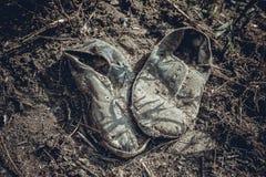 Vieilles espadrilles grises sales abandonnées au sol Photo stock