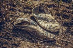 Vieilles espadrilles grises sales abandonnées au sol Photos stock