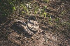 Vieilles espadrilles grises sales abandonnées au sol Photos libres de droits
