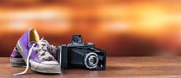Vieilles espadrilles pourpres utilisées avec le vieil appareil-photo Photographie stock