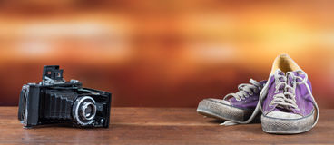 Vieilles espadrilles pourpres utilisées avec le vieil appareil-photo Photos stock