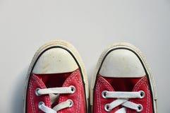 Vieilles espadrilles rouges sur le plancher de tuiles Image libre de droits