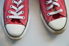 vieilles espadrilles rouges sur le plancher de tuiles blanc Image stock