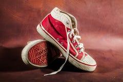 Vieilles espadrilles rouges sur le vieux cuir. Images stock