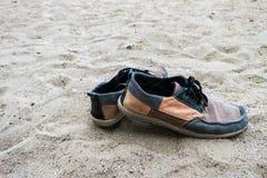 Vieilles espadrilles sur le sable à la plage Fond de cru Photos stock