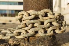 Vieilles et rouillées chaînes autour d'une borne photo stock