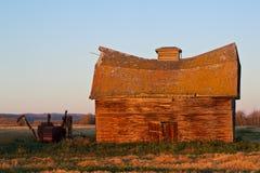 Vieilles grange et moissonneuse abandonnées de rondin dans la chute Photos stock