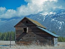 Vieilles grange, pompe à eau de main et montagnes Image stock