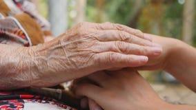 Vieilles mains femelles froissées et jeunes soulageant et se frottant extérieur Dépense de petite-fille et de grand-mère clips vidéos