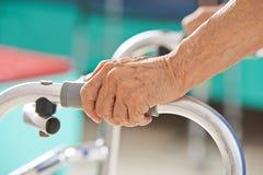 Vieilles mains supérieures sur un marcheur Image stock