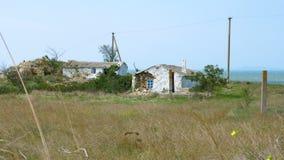 Vieilles maisons blanches détruites sur le pré à côté de la mer clips vidéos