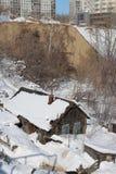 Vieilles maisons en bois délabrées sur le fond des bâtiments modernes ayant beaucoup d'étages urbains photos stock
