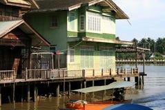 Vieilles maisons vertes en bois sur la rive Image stock