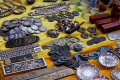Vieilles pièces de monnaie et d'autres articles à vendre sur un marché dans Yunnan, Chine images libres de droits