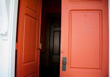 Vieilles portes à deux battants rouges en bois menant dedans à un hall foncé images stock
